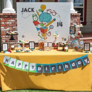 a yellow tablescape covered with desserts and paper decorations for a puzzle themed birthday